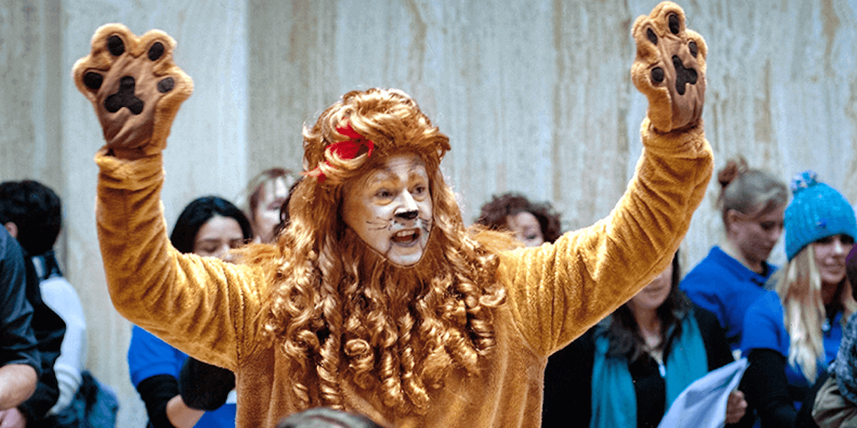 Man dressed in lion costume speaking at a press conference in the Roundhouse